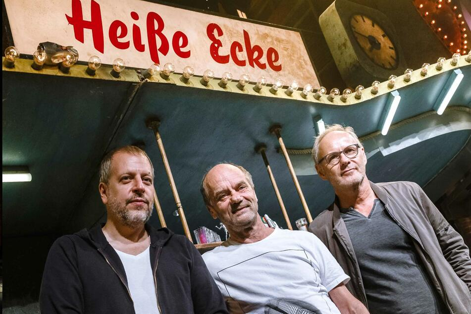 """Lotto King Karl (l.-r.), Musiker und Moderator, Corny Littmann, Theaterdirektor, und Reinhold Beckmann, Fernsehmoderator, stehen im Bühnenbild des Kiez-Musicals """"Heiße Ecke""""."""