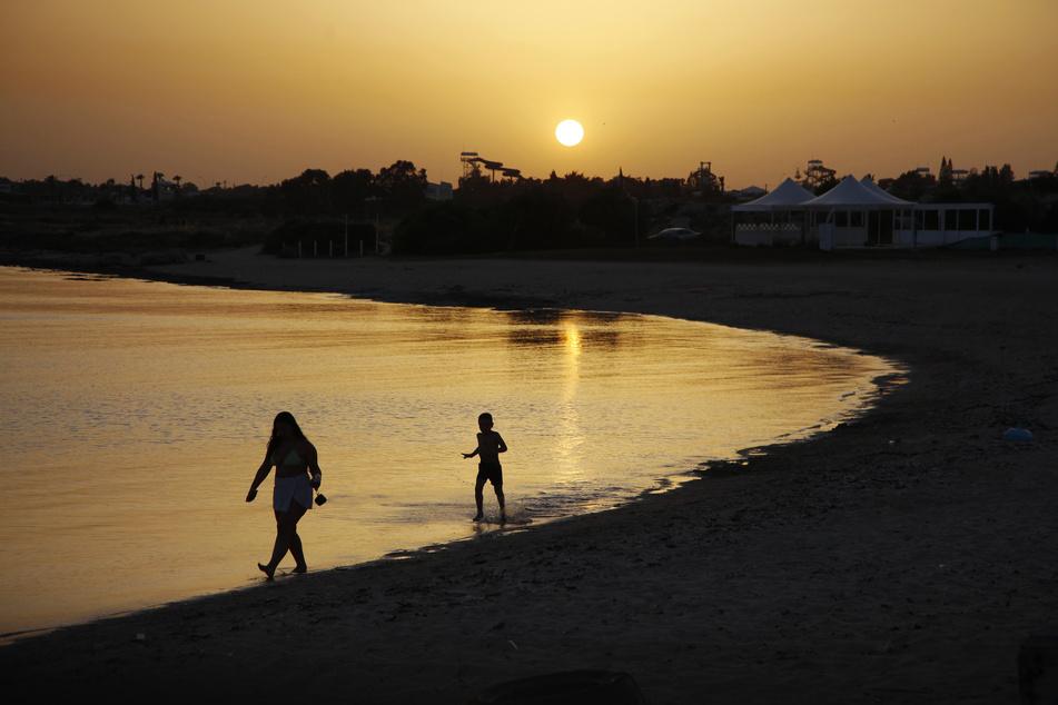 Strandbesucher gehen bei Sonnenuntergang an einem leeren Strandabschnitt des Strandhotels Dome in Zyperns Badeort Ayia Napa spazieren.