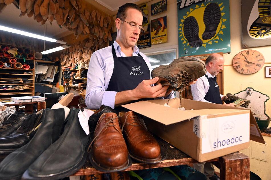 Matthias Vickermann (l.) von der Firma shoedoc arbeitet zusammen mit seinem Kollegen Martin Stoya daran, die Schuhe der Flutopfer wieder auf Vordermann zu bringen.