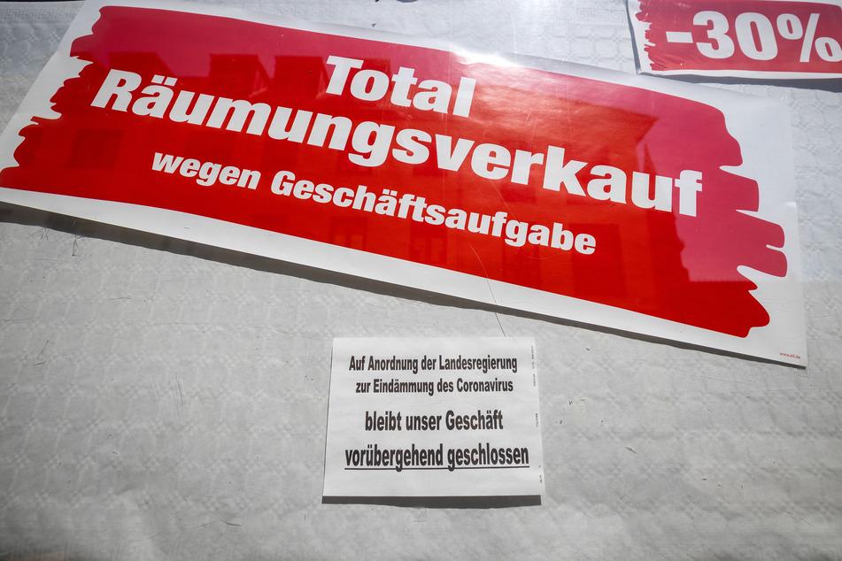 """Thüringen, Meiningen: Ein Schild an einem Geschäft weist darauf hin, dass es auf Anordnung der Landesregierung zur Eindämmung des Coronavirus geschlossen ist, darüber hängt ein weiteres Schild mit der Aufschrift """"Total-Räumungsverkauf wegen Geschäftsaufgabe""""."""
