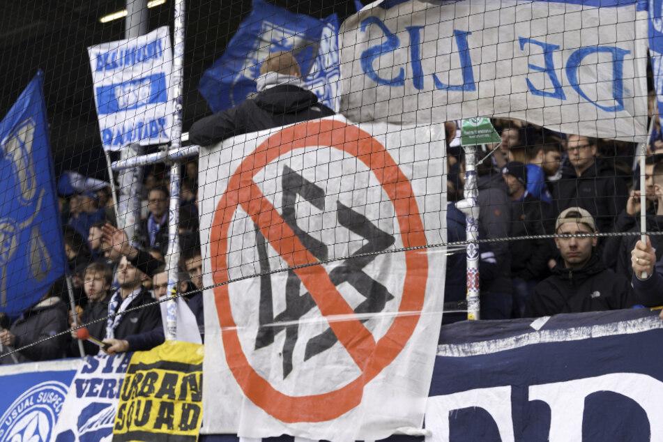 Darmstadt-Fans zeigen ein Transparent , auf dem das DFB-Logo durchgestrichen ist.