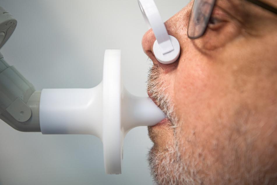 Ein Long-Covid-Patient sitzt zur Überprüfung seiner Lungenfunktion in einem Bodyplethysmographen.