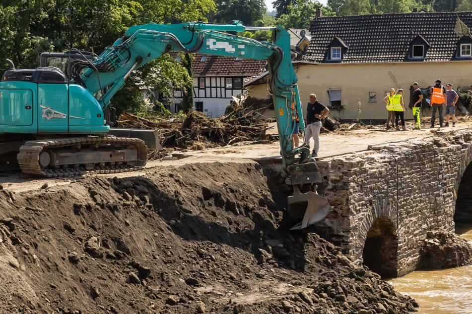 Große Schäden nach der Flutkatastrophe in Rheinland-Pfalz: Ein Bagger verdichtet eine notdürftig geflickte Brücke über den Fluss Ahr.