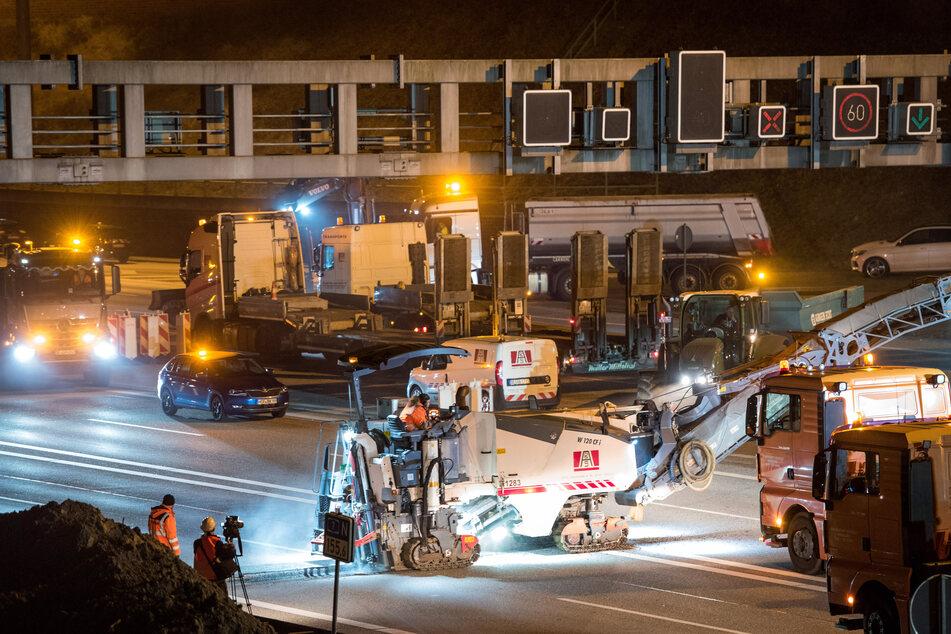 Baufahrzeuge fahren auf der gesperrten Autobahn A7.