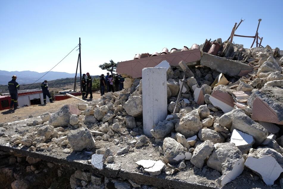 Feuerwehrleute stehen neben der zerstörten griechisch-orthodoxen Kirche Profitis Ilias in Arkalochori.