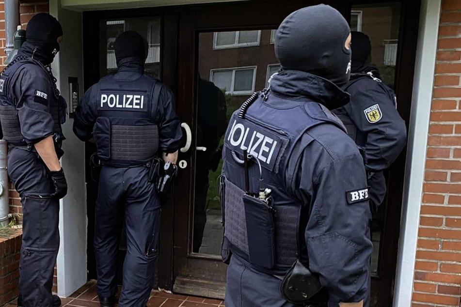 Beamte der Bundespolizei stehen vor einer Haustür. Im niedersächsischen Leer in Ostfriesland und in Rheinland-Pfalz hat die Bundespolizei mehrere Gebäude durchsucht.