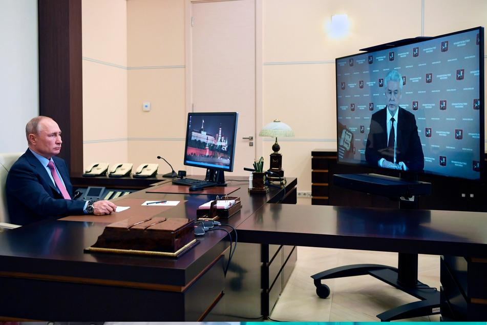 Wladimir Putin (68), Präsident von Russland, sitzt in der Residenz Nowo-Ogarjowo an seinem Schreibtisch und nimmt an einer Telefonkonferenz mit dem Moskauer Bürgermeister Sergej Sobjanin teil.