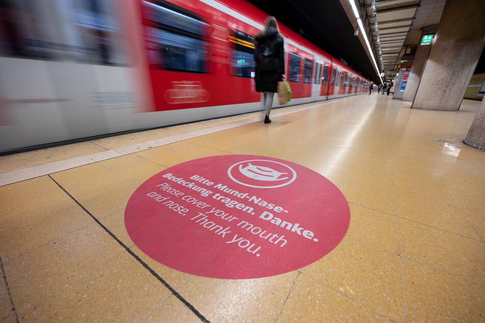 Ein Aufkleber weist in einer S-Bahn Haltestelle auf das Tragen einer Mund-Nasen-Bedeckung hin.