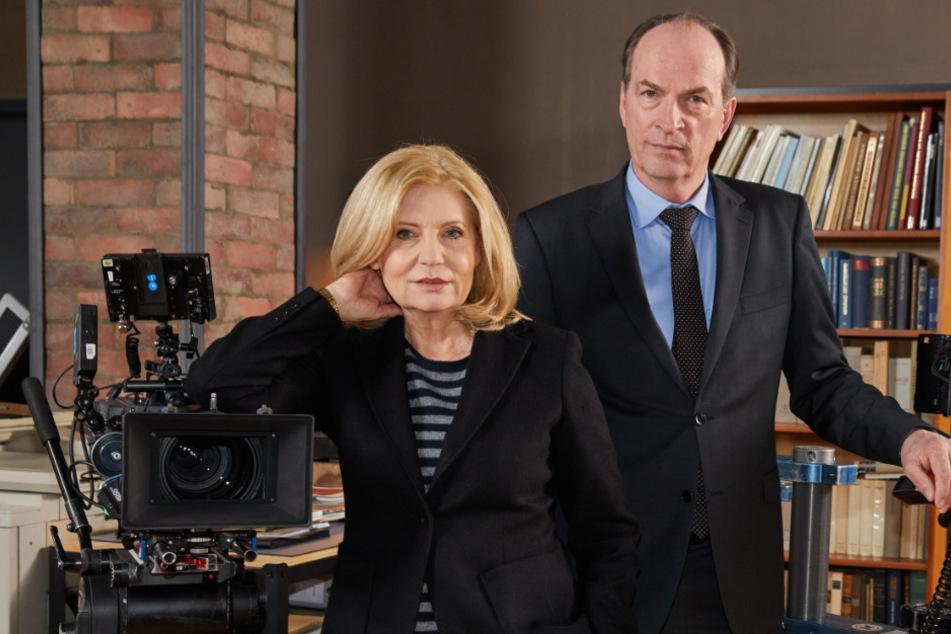 Die Schauspieler Herbert Knaup und Sabine Poste stehen am Filmset.