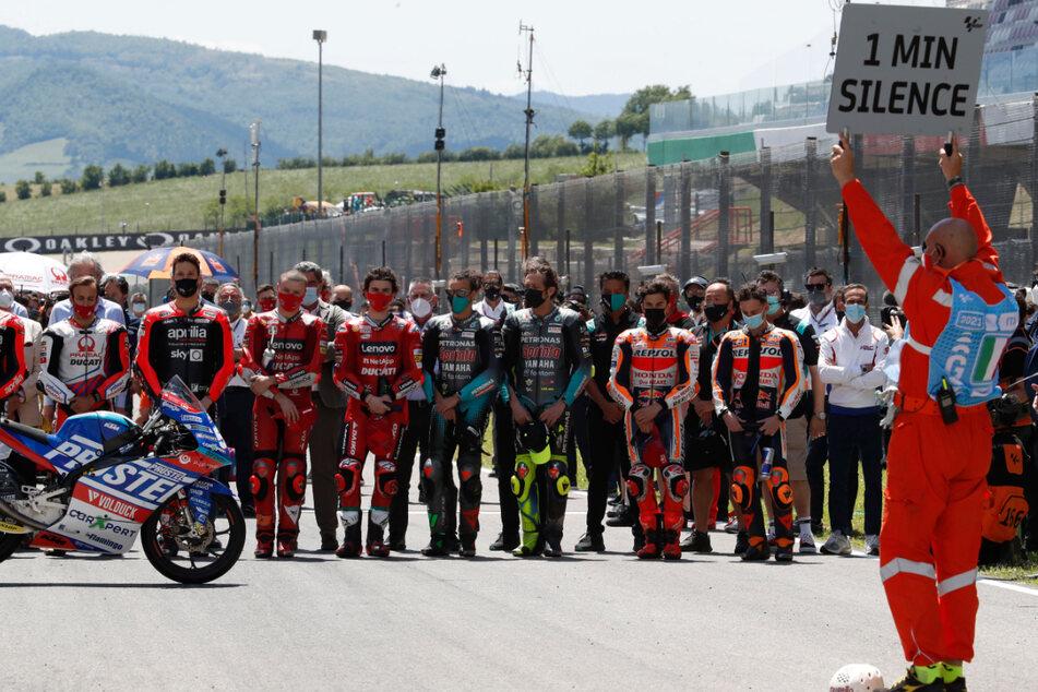 Teamkollegen des verstorbenen Schweizer Rennfahrers Jason Dupasquier stehen hinter seinem Motorrad während einer Schweigeminute vor einem Rennen.