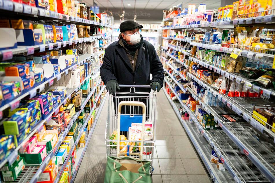 Ein Kunde kauft mit Mundschutz und Handschuhen am frühen Morgen in einem Supermarkt ein.