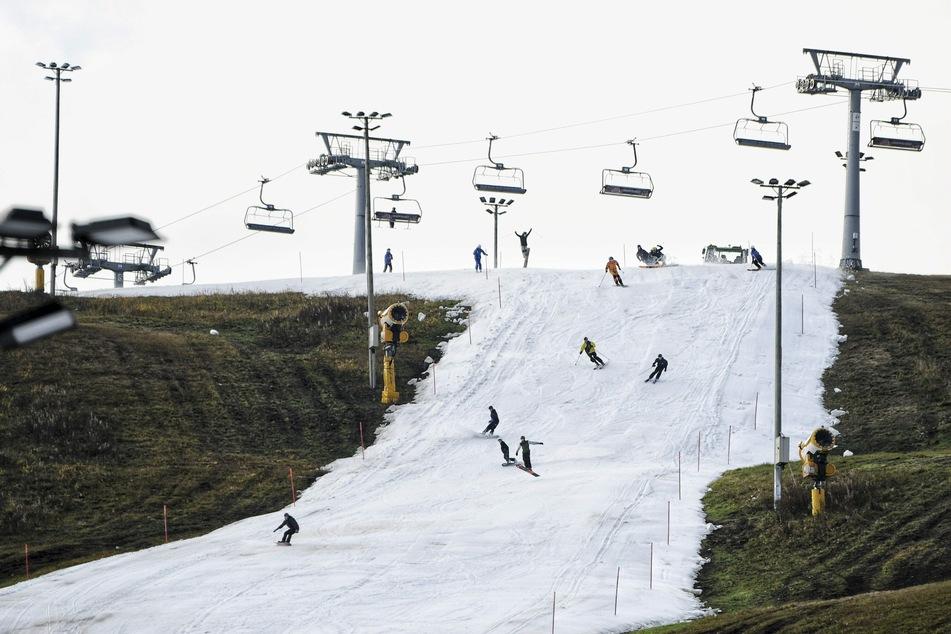 Snowboarder und Skifahrer fahren auf einer Piste.