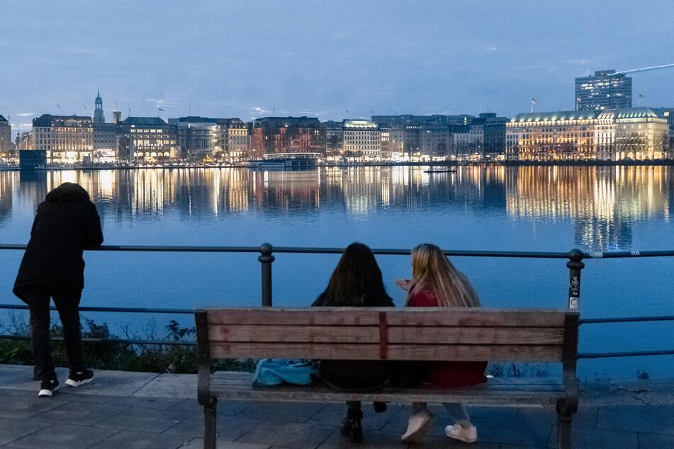 Menschen sitzen und stehen bei milden Temperaturen in der Abenddämmerung an der Binnenalster in Hamburg.