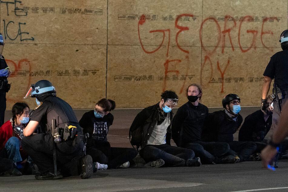 Polizisten verhaften Demonstranten wegen Missachtung der Ausgangssperre.