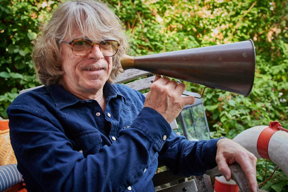 Der Musiker und Komiker Helge Schneider sitzt mit einem Megafon in der Hand auf der Terrasse seiner Wohnung. Schneider hat Finanzminister Scholz (62, SPD) gebeten, die Corona-Hilfe für Künstler anders als ankündigt zu berechnen.