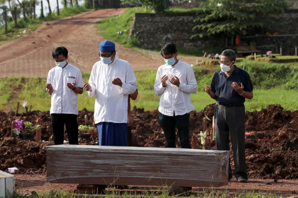 Ein islamischer Geistlicher betet mit Angehörigen bei der Beerdigung eines Mannes in dem Abschnitt eines indonesischen Friedhofs, der für Corona-Verstorbene bestimmt ist.