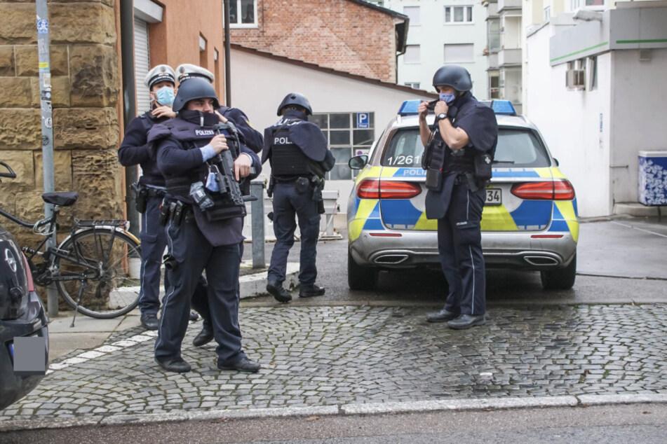 Schwer bewaffnete Polizisten stehen an der Immenhoferstraße in Stuttgart. Ein Mann hatte sich mit einem Messer in seiner Wohnung verschanzt.