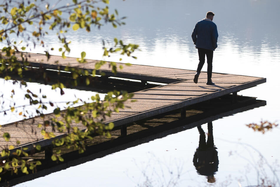 Ein junger Mann geht alleine an einem Steg spazieren. Psychologen warnen im Lockdown vor der Herausforderung, nicht zu vereinsamen.