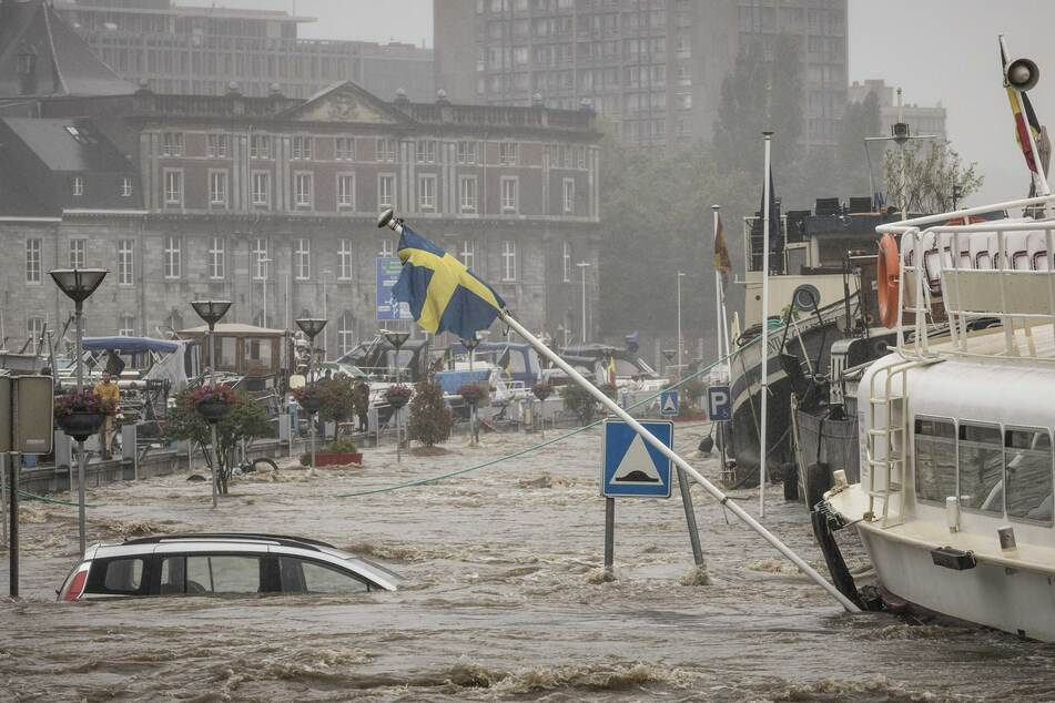 Ein Auto ist komplett vom Hochwasser umgeben, nachdem die Maas über die Ufer getreten ist.