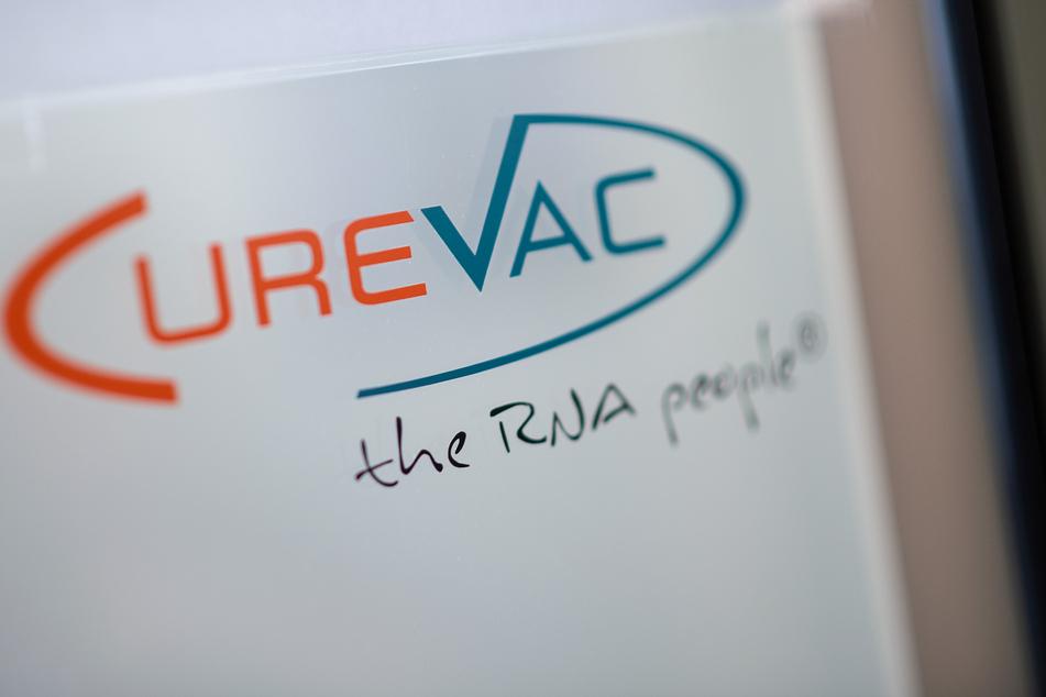 """Tübingen: Das Logo des biopharmazeutischen Unternehmens CureVac steht mit dem Slogan """"the RNA people"""" auf einer Scheibe neben dessen Eingang."""