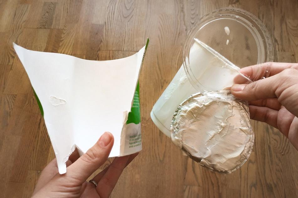 Die Papiermanschette (l.) gehört in das Altpapier, Becher und Deckel in den gelben Sack.