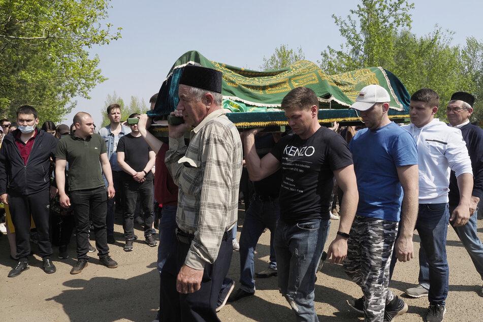 Männer tragen den Sarg einer Englischlehrerin, die bei dem Angriff auf das Gymnasium 175 in Kasan getötet wurde.