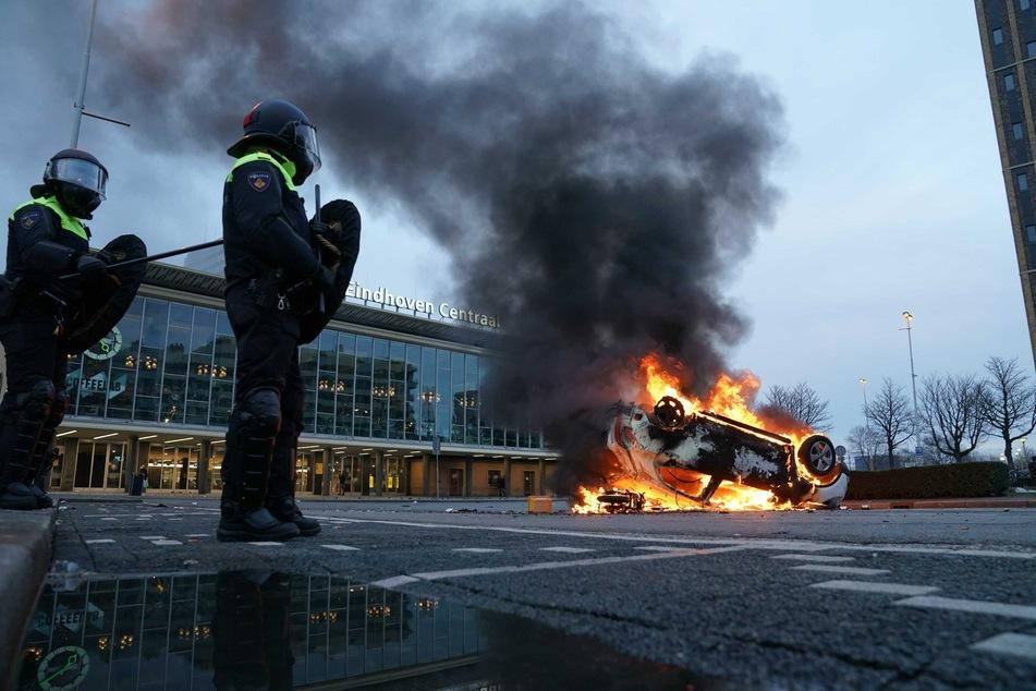 Flammen schlagen aus einem Auto, das vor dem Bahnhof in Eindhofen auf dem Kopf liegt. Mehrere hundert Menschen haben dort am Sonntag gegen die aktuelle Corona-Politik demonstriert.
