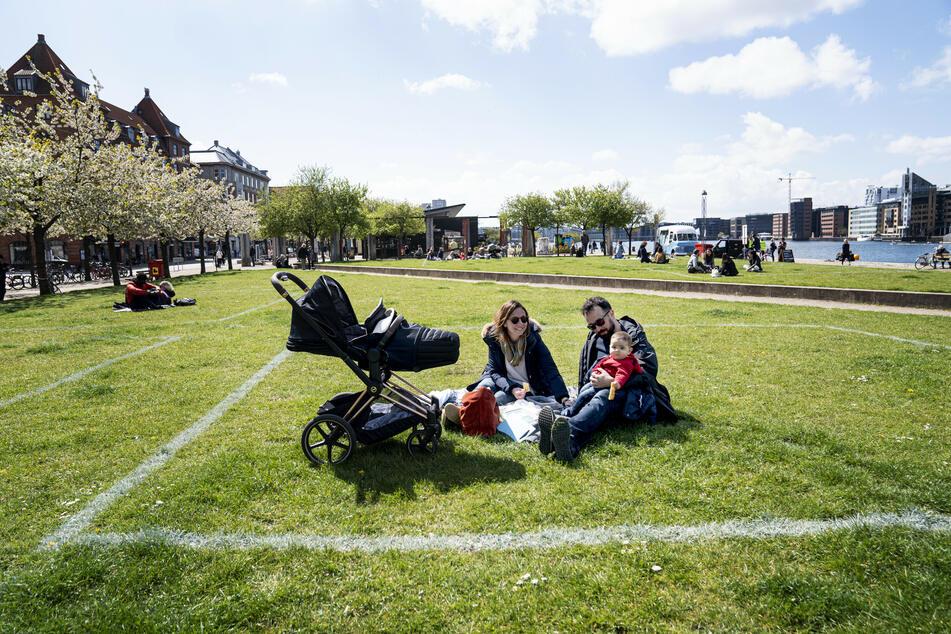 Eine Familie genießt die Sonne im Hafengebiet Islands Brygge. Markierte Flächen auf dem Grasland helfen den Menschen, Abstand voneinander zu halten, wobei etwa 40 Quadratmeter Fläche für maximal 10 Personen markiert sind.