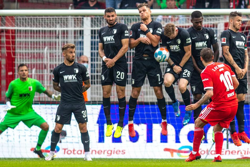 Unions Max Kruse (33, im roten Trikot) bleibt an der Augsburger Mauer hängen. Der FC Augsburg geriet in Zinglers Kritik.