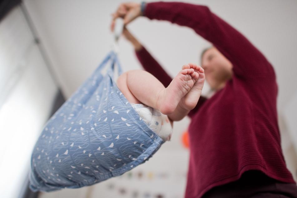 Eine Hebamme wiegt im Rahmen der Nachsorge ein Baby.