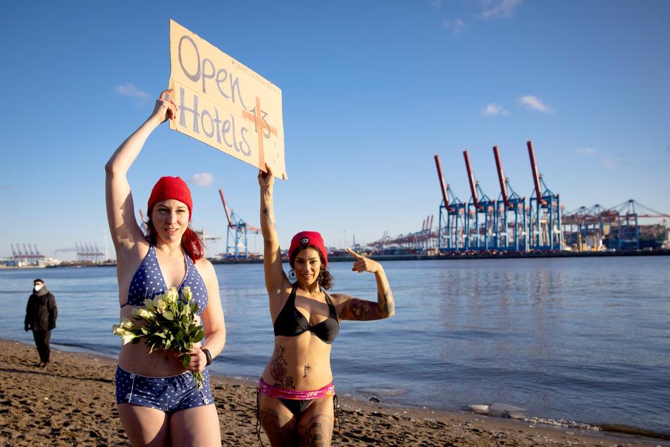 Eve Champagne (l), Burlesque-Künstlerin, und Natalie Warncke halten ein Schild, bevor sie mit anderen Menschen in die eiskalte Elbe springen.
