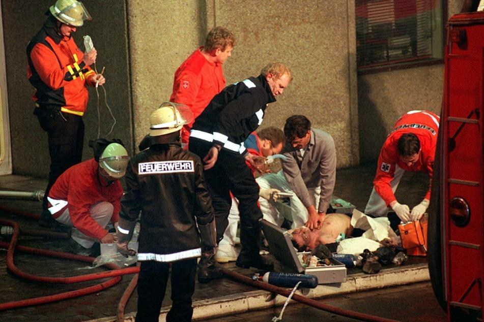 Notärzte und Feuerwehrleute bei der Reanimation eines Verletzten nach dem Brand im Düsseldorfer Flughafen am 11. April 1996. (Archivbild)