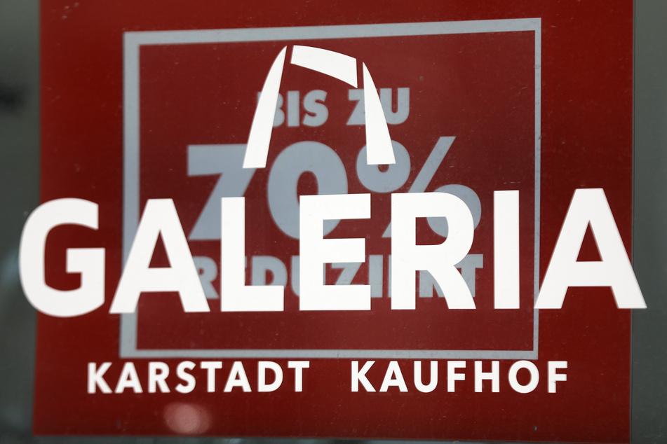 """Das Logo der Warenhauskette Galeria Karstadt Kaufhof hängt in einer Fensterscheibe vor einem Schild """"Bis zu 70 Prozent reduziert""""."""
