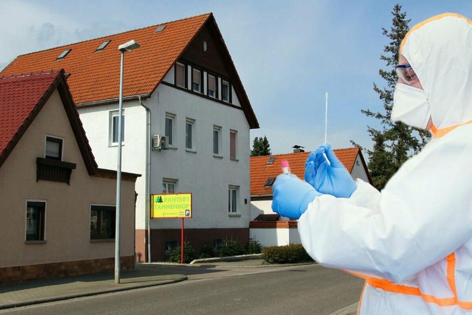 In diesem Haus in Beucha standen nachts plötzlich falsche Corona-Tester vor der Tür. Sie trugen wie der echte Behördenmitarbeiter hier im Foto (r.) weiße Overalls und Atemschutz.