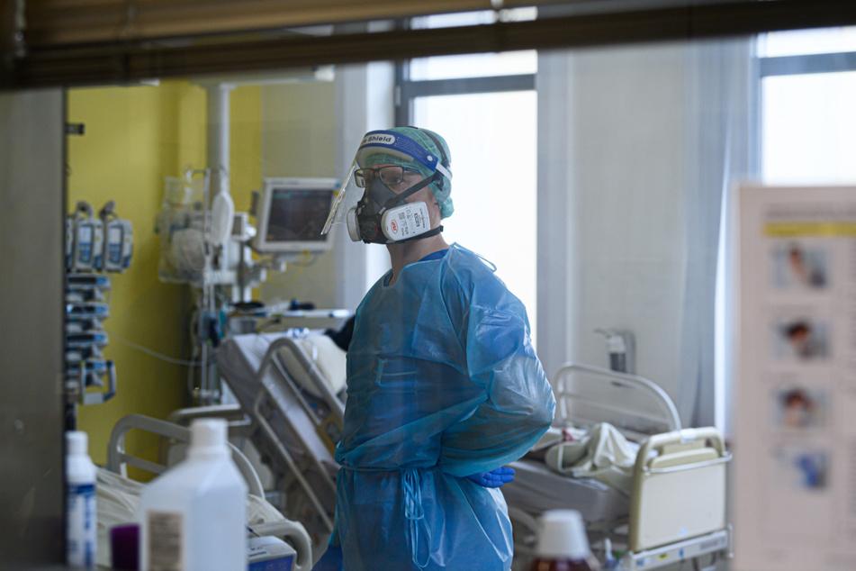 Ein Intensivpfleger ist auf der Covid-19 Intensivstation (ITS) im Städtischen Klinikum Dresden mit der Versorgung von Corona-Patienten beschäftigt.