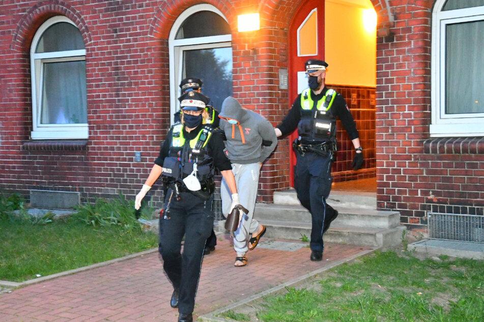 Polizisten führen den festgenommenen Mann ab.