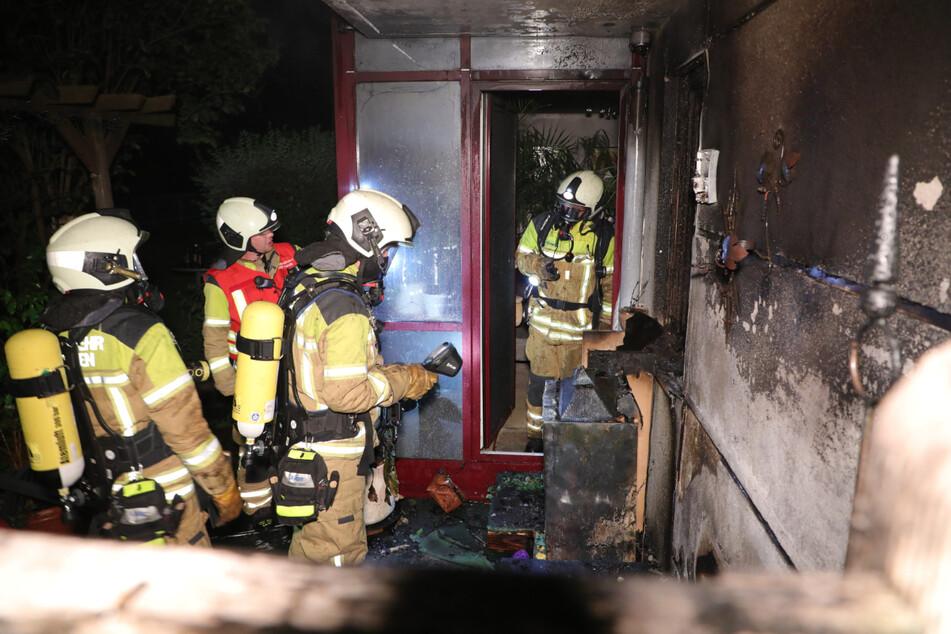 Feuerwehrleute inspizieren die verkohlte Sitzecke nach den Löscharbeiten.