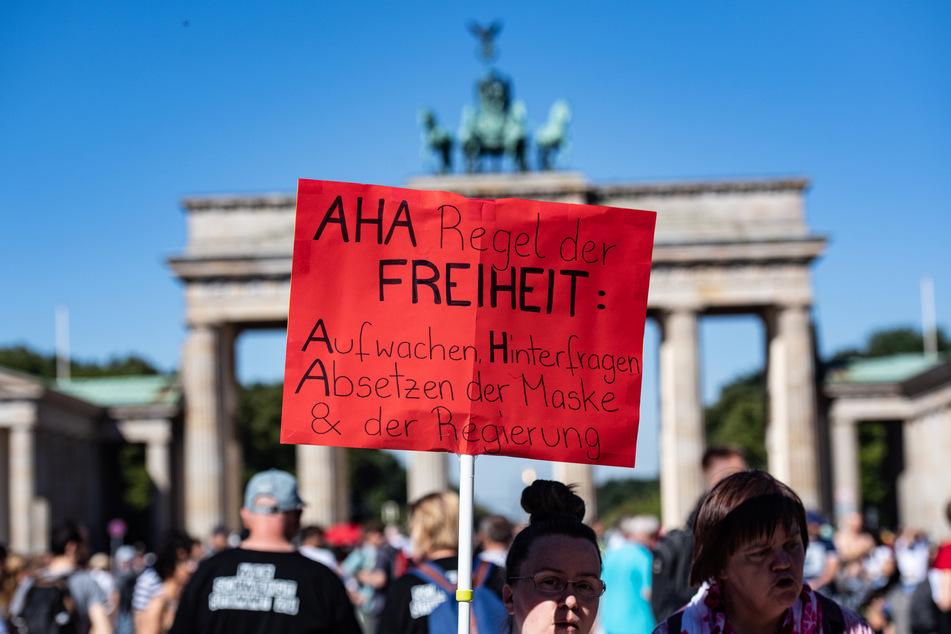 """Ein Schild mit der Aufschrift """"AHA Regel der Freiheit: Aufwachen, Hinterfragen, Absetzen der Maske & der Regierung"""" ragt aus der Menschenmenge bei der Demonstration gegen Corona-Maßnahmen vor dem Brandenburger Tor."""
