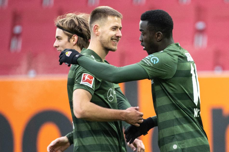 VfB-Abwehrmann Waldemar Anton (l., 24) gratuliert Silas Wamangituka (r.) zu seinem Treffer zum 2:0 gegen den FC Augsburg. Dahinter schleicht sich Vorlagengeber Borna Sosa (22) davon.