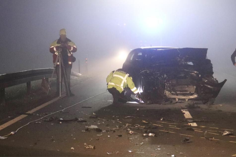Beamte am Wrack des völlig demolierten 1er BMW.