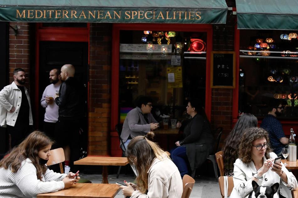 Großbritannien, London: Menschen sitzen und trinken vor einem Restaurant in Soho. (Archivbild)