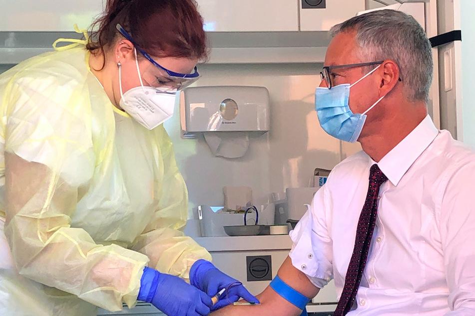 Der Oberbürgermeister von Straubing, Markus Pannermayr (CSU, r), lässt sich eine Blutprobe entnehmen.