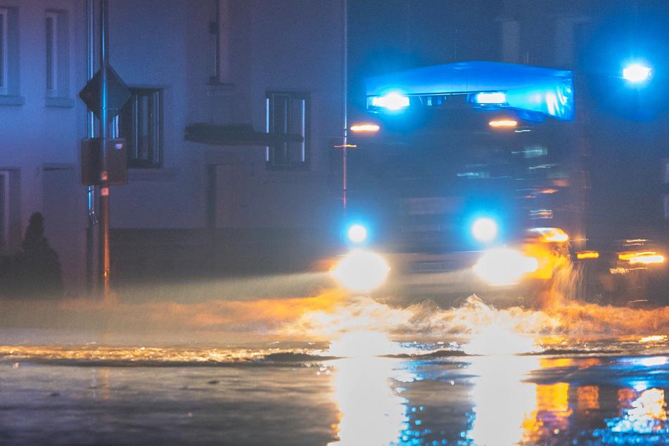 Ein Feuerwehrfahrzeug fährt in der Nacht durch die von der Kyll überflutete Bahnhofstrasse in Kordel – der Ort ist inzwischen durch die Fluten vom Umland abgeschnitten.