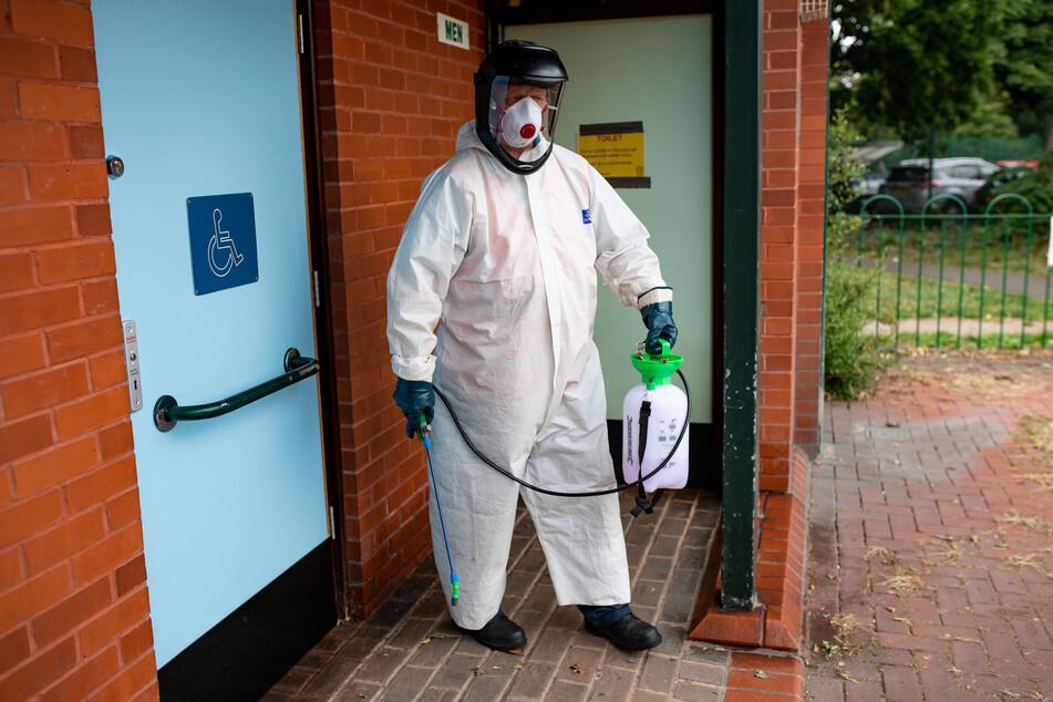 Leicester: Ein Mitarbeiter des Stadtrats in Schutzkleidung desinfiziert eine öffentliche Toilette, nachdem der britische Gesundheitsminister Hancock nach einem Abstieg der Covid-19-Infizierten in der Stadt einen Lockdown verhängt hat.