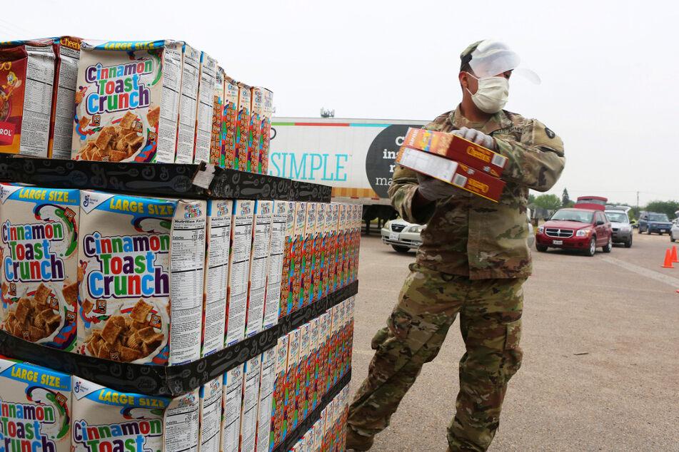 Ein Mitglied der Nationalgarde von Texas trägt wegen des Coronavirus eine Maske und ein Visier, während er in Pharr bei der Verteilung von Nahrungsmitteln hilft. Es wurden Lebensmittelpakete an Anwohner verteilt.