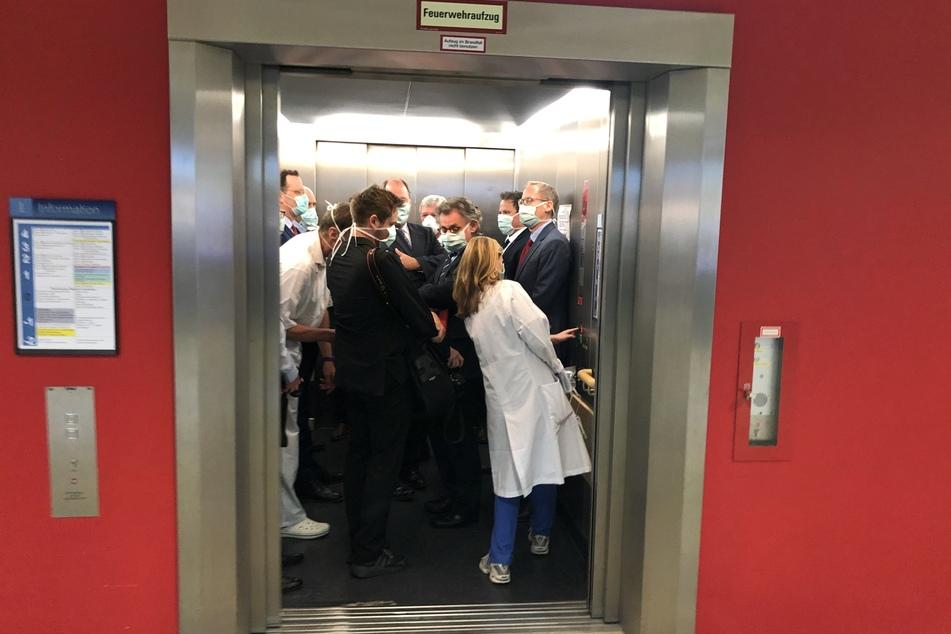 Bei einem Besuch der Uniklinik Gießen drängen sich Bundesgesundheitsminister Jens Spahn (CDU, l.), und Hessens Ministerpräsident Volker Bouffier (CDU, m.) mit Begleitern in einem Fahrstuhl.