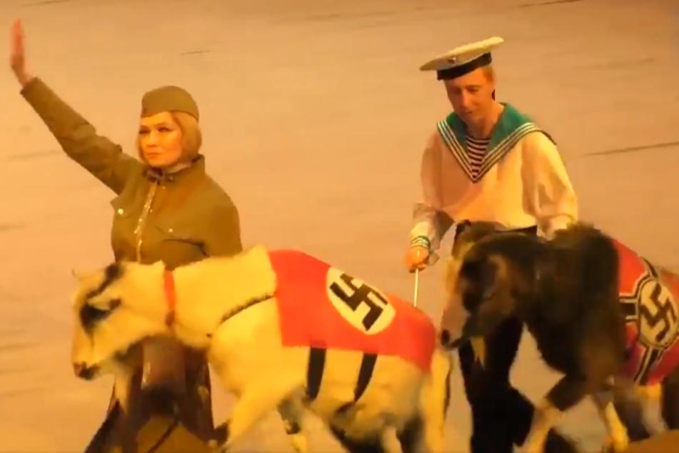 Mit Hakenkreuzen bedeckte Ziegen werden durch die Manege geführt.