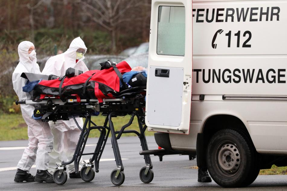 Ein gerade in Rostock angekommener Corona-Patient wird in einen Rettungswagen geschoben.