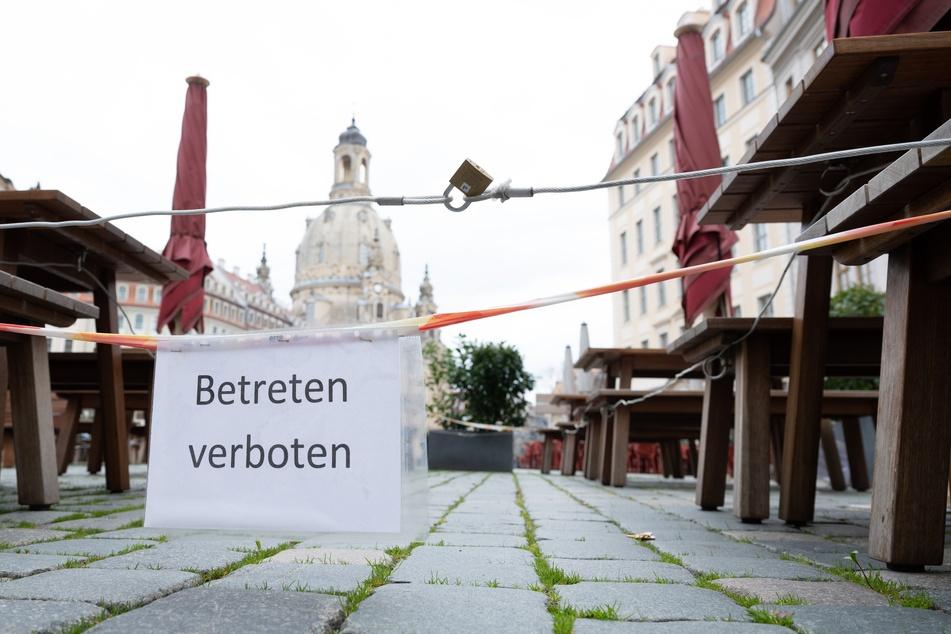 """Ein Schild mit der Aufschrift """"Betreten verboten"""" hängt auf dem Neumarkt vor der Frauenkirche an einer Terrassenbestuhlung vor einem geschlossenen Restaurant. Die Corona-Inzidenz in Dresden sank innerhalb der vergangenen 24 Stunden leicht ab."""