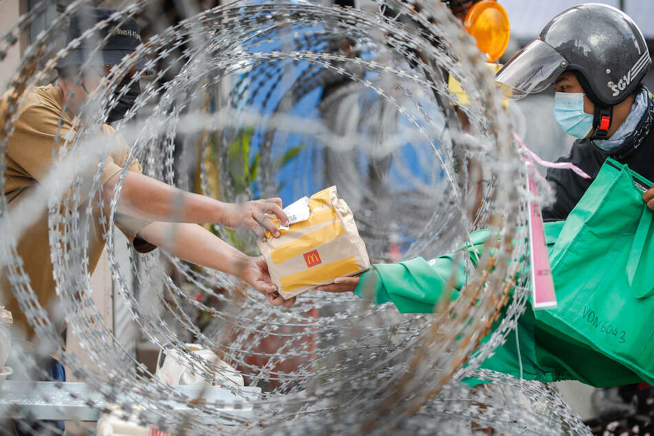 Ein Bewohner in Kuala Lumpur erhält eine Tüte von einem Essenslieferanten durch einen Stacheldraht in der Wohnsiedlung Segambut Dalam. Aufgrund eines Anstiegs der täglich gemeldeten Corona-Neuinfektionen hat die Regierung Malaysias begonnen, die Bewegungskontrolle weiter zu verschärfen und einen strengeren Lockdown zu verhängen.